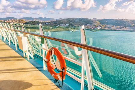 Voyage de vacances en bateau de croisière destination des Caraïbes. Vue sur l'île depuis le pont du balcon du bateau avec balustrade et bouée de sauvetage rouge. Escapade tropicale en mer.