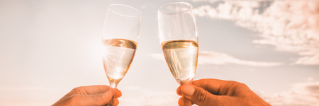 Couple toasting wine glasses for celebration. Champagne toast in luxury restaurant. Two people holding flutes doing cheers. Banner panorama crop on sunset background. Stock Photo