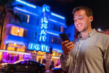 Miami man texting phone walking on Ocean drive South Beach Florida. Art Deco hotels and restaurants at night world famous tourist destination for nightlife. Smartphone travel night lifestyle. 스톡 콘텐츠