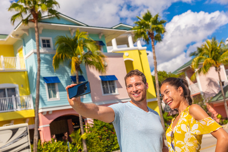 Selfie photo couple tourists taking picture with smart phone in Fort Myers, Florida at colorful wood beach cottages. USA summer travel lifestyle. Asian woman and Caucasian man smiling at mobile phone.