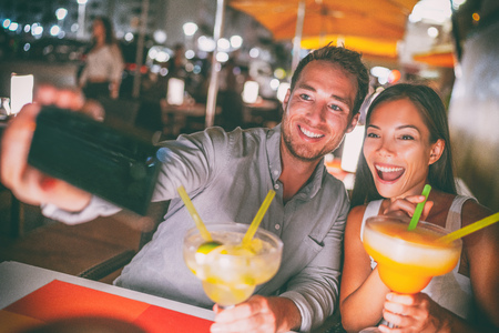 Fun date night out young people taking selfie of themselves drinking giant margaritas cocktails party couple going out on Miami Ocean drive restaurant. Funny drinks outdoor terrace travel lifestyle.
