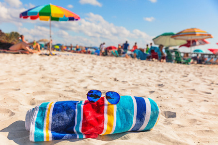 Beach towel and fashion sunglasses on Florida beach background -summer vacation travel concept copy space. Crowded popular USA destination for american holidays.