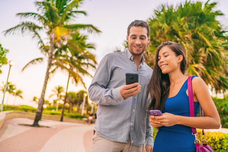 Happy young couple people lifestyle using their cellphones outside on tropical miami beach street. Interracial relationship tourists holding mobile phones texting or searching online for destination. Imagens