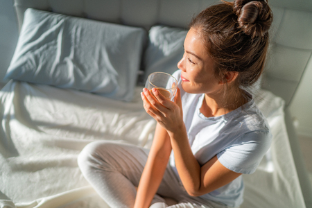 Morning breakfast in bed happy Asian woman drinking hot coffee mug relaxing sitting on mattress. Weekend relaxation wellness. Stockfoto
