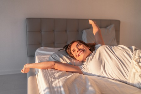 Happy girl waking up in the morning sunshine looking at sunrise sun in window excited to enjoy the day. Wake up energetic Asian woman lying in bed well rested from a good night sleep. Archivio Fotografico