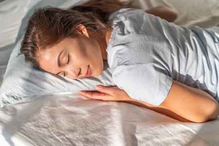 Fille asiatique de lit dormant sur le dormeur d'estomac se reposant la tête sur l'oreiller de mousse. Banque d'images