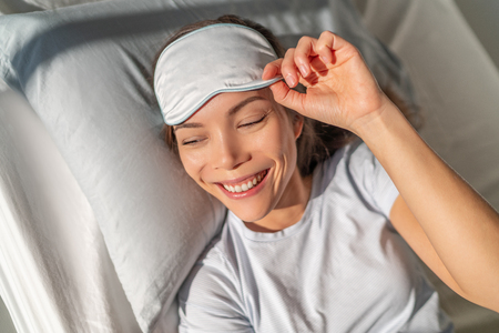 Happy Asian woman waking up feeling refreshed from beauty sleep eye sleeping mask for a good nights rest. Smiing young biracial girl in bed. Healthy sleep pillow comfort.