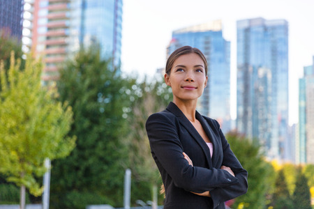 Asian businesswoman. Happy business woman portrait pensive looking up contemplative of her career. City job employment. Chinese professional in black suit confident with crossed arms. Stock fotó - 118452303