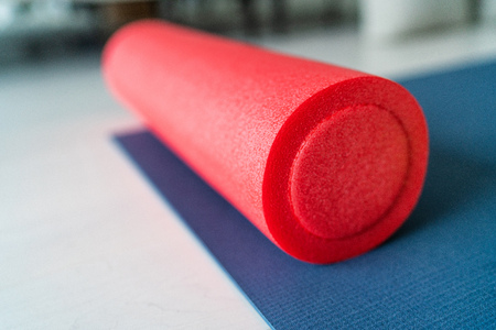 Foam roller fitness equipment on exercise mat gym floor. Indoors closeup of sports object, accessory for athletes to massage tired and tense muscles. 免版税图像