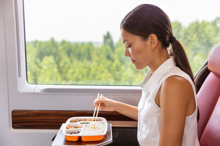 Train commute bus travel Asian business woman eating asian food meal with chopsticks. Businesspeople commuting eating lunch. Stock Photo