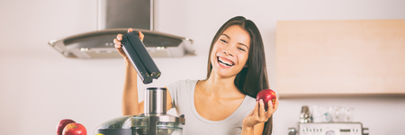 Apple juice - Woman making apples smoothie on juicer machine at home in kitchen. Juicing and healthy eating happy Asian woman cooking green vegetable and fruit juice. Banner panorama. Stock Photo