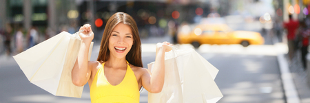 Shopping woman holding bags of clothes on outdoor street smiling. Happy customer chinese girl spending money in NYC New York City banner panorama. Shop lifestyle.