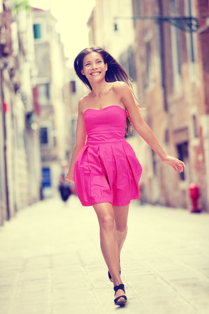 Woman in pink fashion dress walking in in Venice, Italy cheerful and happy . Pretty sexy brunette fashion model girl in her 20s.