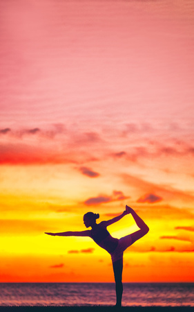 Yoga silhouette of woman stretching doing dancers pose in beautiful dusk colors at sunset on beach background. Copy space on pink sky clouds. Wellness meditation concept. Standard-Bild