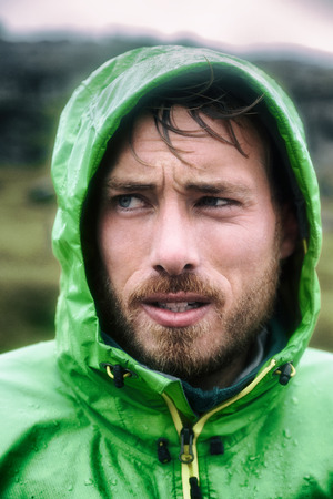 Hiker man on extreme hike adventure outdoor raining wearing waterproof rain jacket hood. Portrait of rugged scandinavian young adult sportsman outside.
