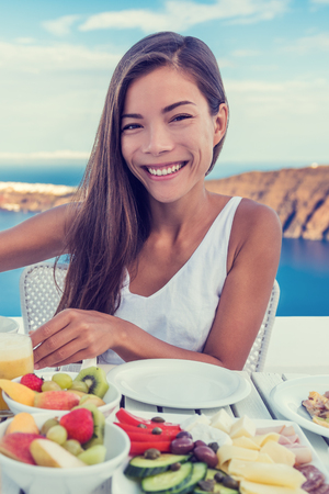 Woman eating healthy breakfast at restaurant table with Mediterranean sea view background from hotel terrace. Smiling Asian girl, vegetarian fruits and vegetables food retreat. Stock Photo