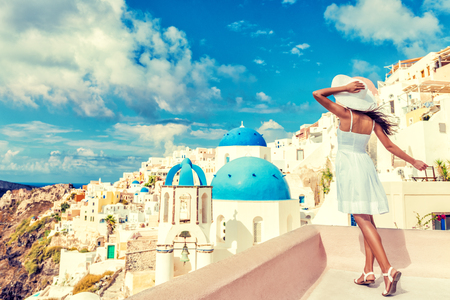 Travel Santorini luxury cruise vacation woman tourist looking at famous Europe destination - Sun summer holiday lifestyle.