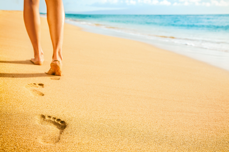 Beach woman legs feet walking barefoot on sand leaving footprints on golden sand in sunset. Vacation travel freedom people relaxing in summer. Banco de Imagens