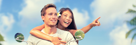Happy tourists riding motorcycle on Caribbean vacation holiday. Girl pointing to the side looking at tourist attraction. Summer road trip travel getaway. Young couple banner panorama.