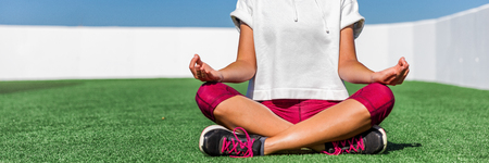Yoga fitness sport woman meditating in lotus pose sitting on grass. Panorama banner crop of activewear leggings and shoes. Lower body legs and feet.
