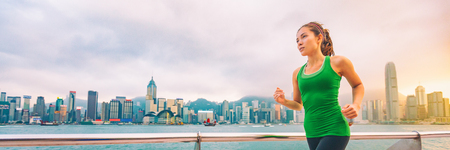 Hong Kong city China travel sightseeing fitness woman jogging at skyline banner panorama . Healthy active lifestyle panoramic view of urban landscape.