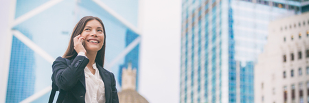 Asian businesswoman talking on mobile phone in Hong Kong cityscape background panoramic banner. Young chinese woman calling on smartphone happy. Multiracial Chinese Caucasian lawyer.