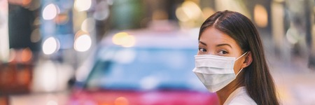 Flu virus protection mask protective against influenza sickness viruses and disease. Sick sian woman wearing surgical face mask in public spaces. Healthcare banner panorama concept. Stock Photo