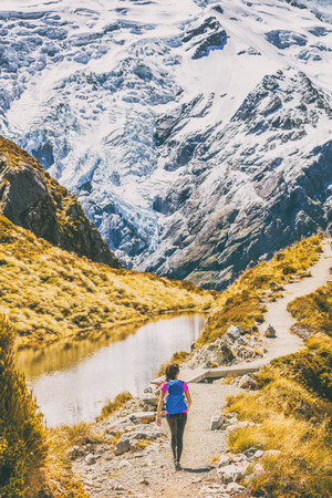 Hiking girl in New Zealand Mt Cook nature mountain. Alone hiker walking on popular trail Mueller Hut route in Mount Cook National Park mountains. Stock Photo