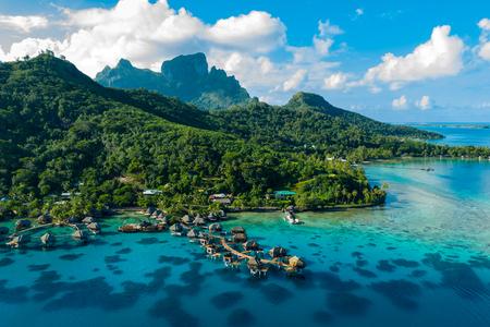 Bora Bora aerial drone video of travel vacation paradise with overwater bungalows luxury resort, coral reef lagoon ocean beach. Mount Otemanu, Bora Bora, French Polynesia, Tahiti, South Pacific Ocean Archivio Fotografico