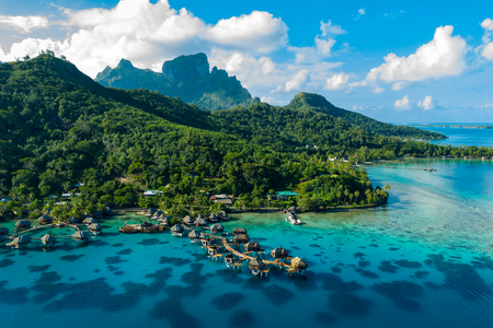 Bora Bora aerial drone video of travel vacation paradise with overwater bungalows luxury resort, coral reef lagoon ocean beach. Mount Otemanu, Bora Bora, French Polynesia, Tahiti, South Pacific Ocean Фото со стока