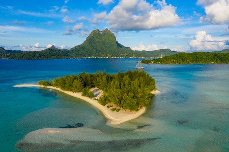 Bora Bora in French Polynesia. Aerial view of Motu Tapu paradise island and turquoise blue water in coral reef lagoon and Mt Pahia, Mount Otemanu, Tahiti, South Pacific Ocean.