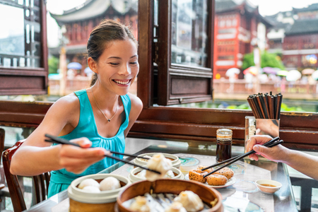 Chinese woman eating at Shanghai restaurant Xiao long bao  xiaolongbao soup dumplings typical food China travel vacation. Asia tourist girl eating Shanghainese steamed dumpling buns with chopsticks.