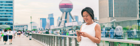 Phone Asian businesswoman texting online in China banner panorama. Middle aged woman using cellphone on Shanghai city street. Mature people lifestyle. Businesswoman holding mobile phone working.