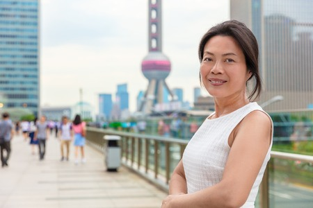 Asian middle age woman model smiling happy in Shanghai city street. Chinese mature businesswoman China professional.