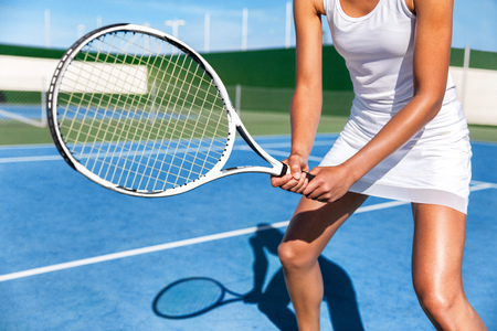 Tennis player woman ready playing game on blue hard court holding racket in position wearing white dress skirt. Female athlete sport girl in summer sports activity class. Stok Fotoğraf