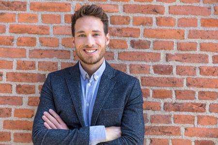 Portrait d'homme d'affaires confiant jeune entrepreneur d'affaires homme regardant la caméra contre la texture du mur de briques urbaines. Adulte mâle caucasien souriant.
