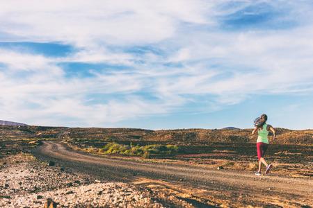 Entraînement de remise en forme dans le volcan paysage en plein air. Femme d'athlète courant sur le chemin de course de traînée dans le fond volcanique au coucher du soleil.