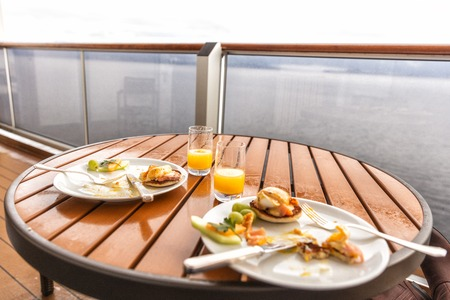 Cruise ship room balcony breakfast plates with fruits and eggs eaten. Real candid snapshot of half eaten food finished meals in the morning on Alaska travel. 版權商用圖片 - 121627365