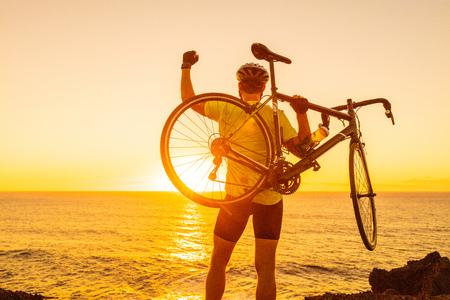 Successo, successo e concetto vincente con la bici da strada dell'uomo ciclista. Felice maschio atleta professionista in bicicletta alzando le braccia sollevamento bici dal mare durante il tramonto tifo e festeggiare in cima al vertice.