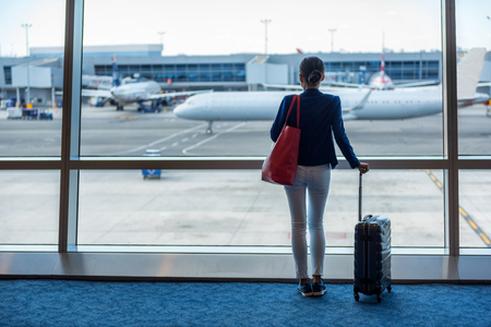 Businesswoman traveling in airport. Woman looking through the window at tarmac and planes waiting for flight. Business travel concept. 스톡 콘텐츠
