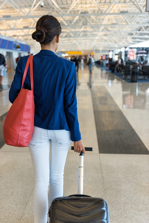 Woman traveler walking through airport terminal going to gate carrying purse and carry-on hand luggage for flight travel.