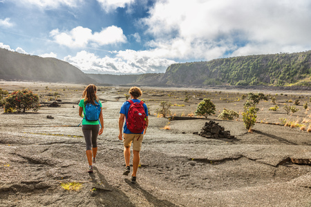 Couple tourists hikers walking on Kilauea Iki crater trail hike in Big Island, Hawaii. USA summer travel vacation destination for outdoor nature adventure, american tourism.