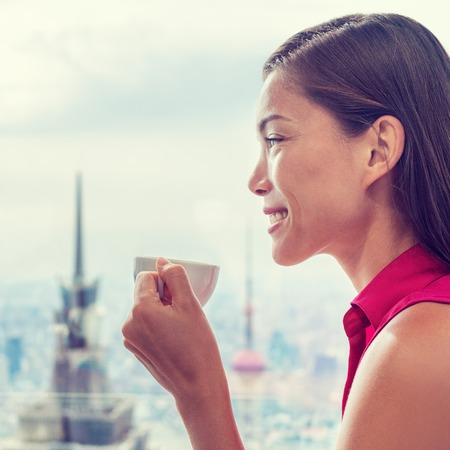 Asian woman enjoying afternoon high tea in luxury cafe or high end restaurant with city view of Shanghais skyline. Chinese businesswoman lady drinking hot cup of coffee relaxing. Фото со стока