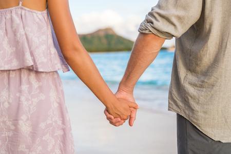 Honeymoon travel beach vacation couple holding hands in sunset. Newlyweds in love. Waikiki beach in Honolulu, Hawaii. Stock Photo