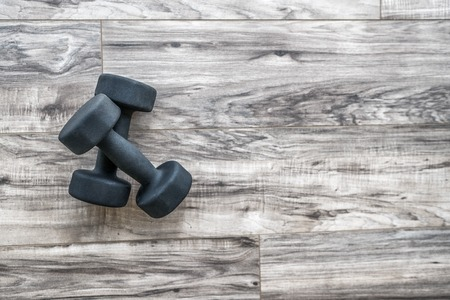 Training at home fitness concept: dumbbell weights on wood floor at fitness gym . Weight loss and health. Sport fit lifestyle. Standard-Bild