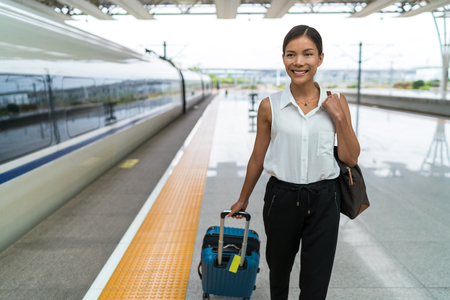 Asian businesswoman with carry-on hand luggage leaving train platform after transport. Morning commute to work or travel.