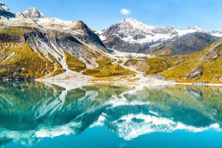 Parque Nacional Glacier Bay, Alaska, Estados Unidos. Increíble paisaje glaciar que muestra los picos de las montañas y los glaciares en un día de verano de cielo azul claro. Reflejo de espejo de montañas en tranquilas aguas glaciares.