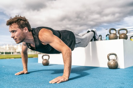 Decline push Up fitness man doing strength training exercise pushup at outdoor gym with elevated legs on jump box. Stock Photo