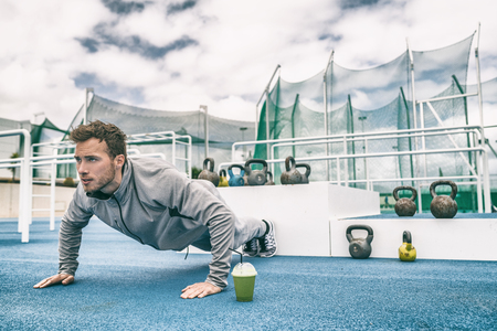 Push up fit man doing arm workout exercising bodyweight exercise pushup outdoor in stadium gym with kettlebells.