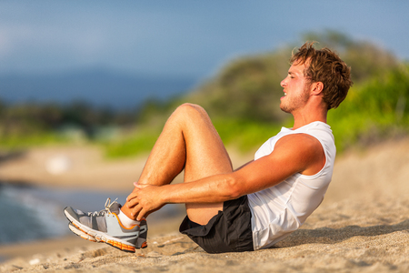 Abs workout fit man doing crunches on beach. Situps training easy weight loss for fat belly male athlete working out.